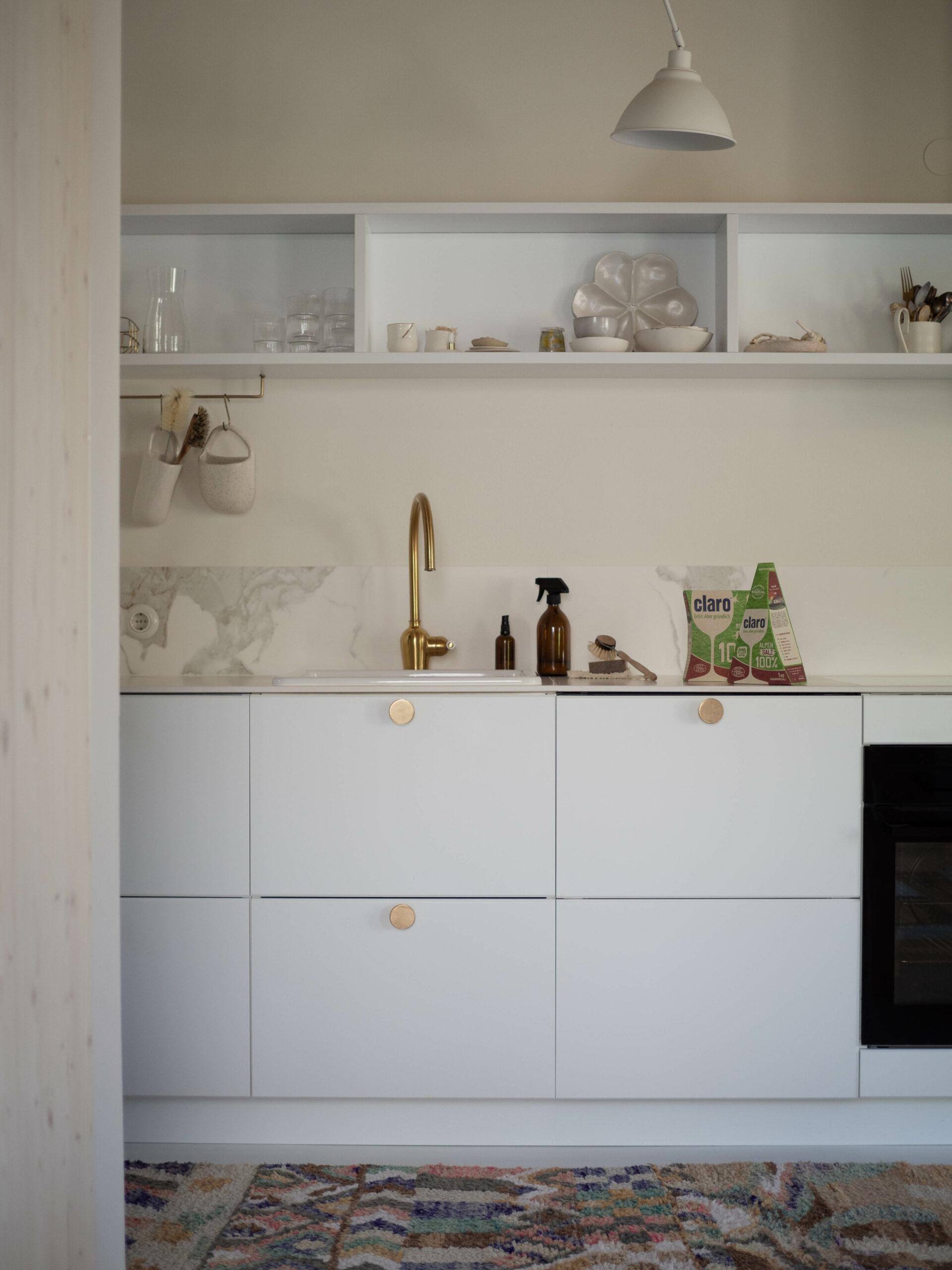 Weiße Küche mit Goldakzenten und Marmor-Keramikplatte